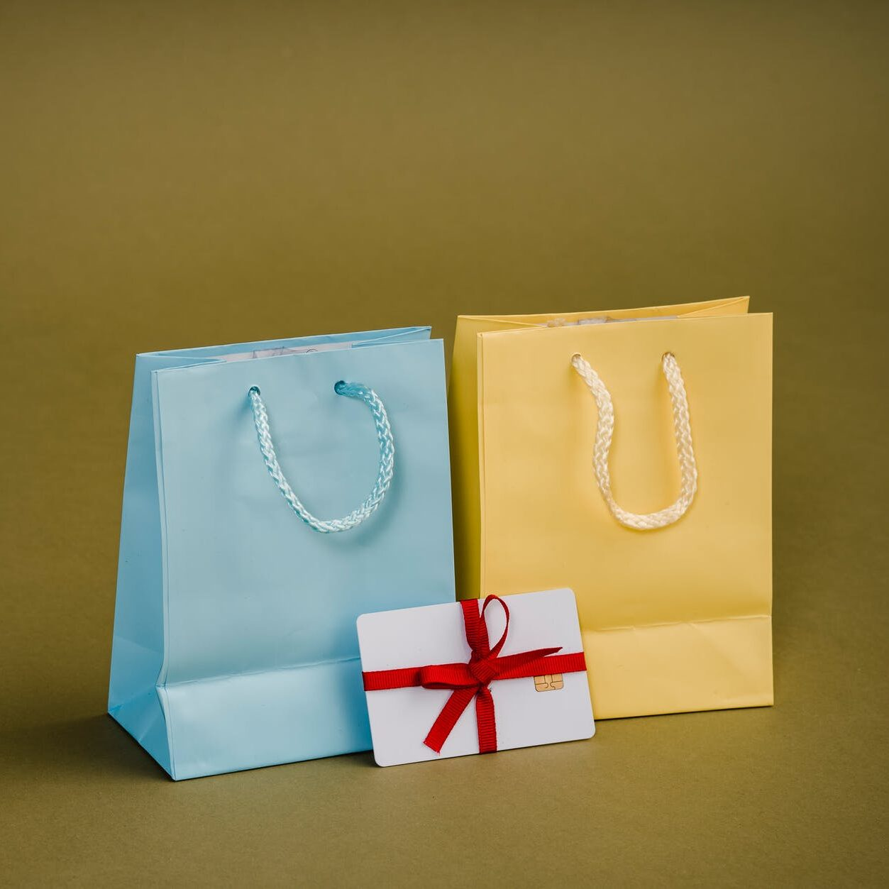 assorted gift bags with cords on brown background