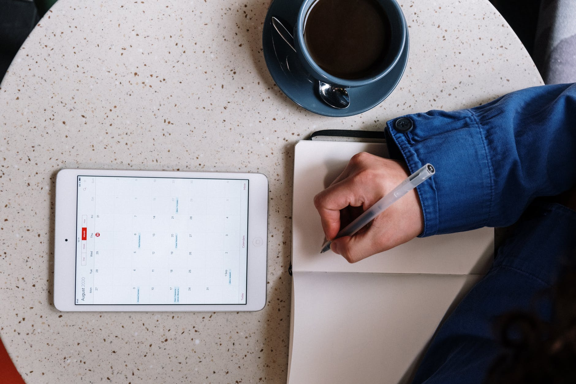person holding pen and checking calendar on tablet